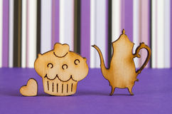 Wooden icons of cake and teapot with little heart on purple stri Stock Photography