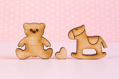 Wooden icons of Teddy bear and children's rocking horse with lit Royalty Free Stock Images