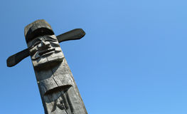 Wooden idol. Smiling wooden idol on the background of blue sky Stock Images