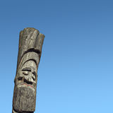 Wooden idol - Jangseung. Smiling wooden idol on the background of blue sky Royalty Free Stock Images