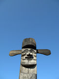 Wooden idol - Jangseung. Smiling wooden idol on the background of blue sky Stock Photography