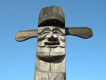 Wooden idol - Jangseung. Smiling wooden idol on the background of blue sky Stock Image