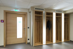 Wooden illuminated garderobe next door. With clothes hanger Royalty Free Stock Photography
