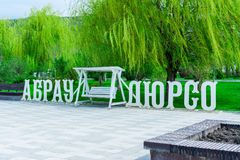 A wooden inscription of Abrau-Durso of white color and a spacious swing between the words against the background of green stock image
