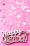 Wooden inscription happy birthday on a pink background stock image