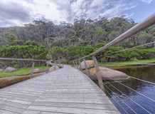 Wooden and iron bridge. A low angle view of a wooden and iron bridge over a river leading to a small forested area in the far shore with partially submerged Royalty Free Stock Photo