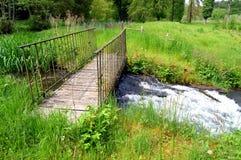 Wooden and iron footbridge on a course of eau. Stock Photos