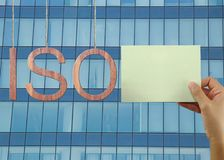 Wooden ISO text Stands for International Organization for Standa. Rdization hanging on rope and businessman hold a green paper on Skyscraper background Royalty Free Stock Photo
