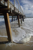 Wooden jetty. Disappearing into distance with white foamy water Stock Images
