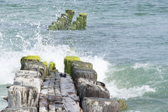 Wooden jetty in Atlantic Ocean. Wooden jetty with wave crashing over it in the atlantic ocean Stock Photos