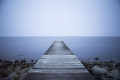 Wooden jetty with blue water. Wooden jetty pointing to  calm blue water and blue sky Royalty Free Stock Images