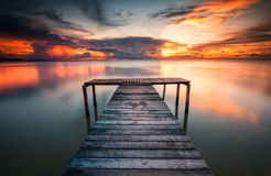 A wooden jetty with bright sunset background Stock Photos
