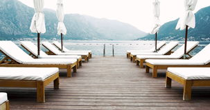 Wooden jetty with deck-chairs and sun umbrella in sea surrounded by mountains – summer resort vacation 4k video background stock footage