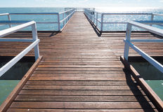 Wooden jetty extending out to sea. A view of a wooden jetty in Hervey Bay, Queensland, Australia Royalty Free Stock Images
