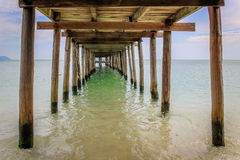 Wooden jetty extending into the sea. Photograph taken from underneath Stock Image