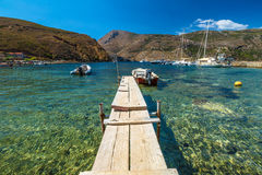 Wooden Jetty. With fishing boats in the clear tropical waters of Porto Kagio, Mani Peninsula, Lakonia, Peloponnese, Greece Stock Images