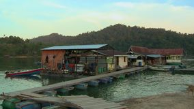 Wooden Jetty | Floating Houseboats, Temenggor Lake. Wide low-angle still shot of a wooden jetty made from plastic tanks leading to floating house boats stock footage