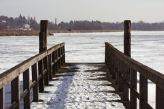 Wooden jetty on frozen river Royalty Free Stock Image
