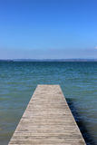 Wooden jetty going out into a blue lake. royalty free stock photos