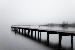 Wooden jetty in the grey. At the top end of the lake of Lucerne in Central Switzerland there's a very picturesque wooden jetty Stock Images
