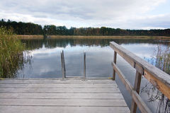 Wooden jetty and ladder into lake Royalty Free Stock Image