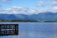 Wooden jetty into the lake with mountain range background. In New Zealand Stock Photos