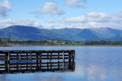 Wooden jetty into the lake with mountain range background. In New Zealand Stock Image