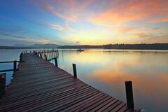 Wooden jetty on  lake at sunset
