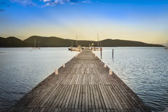 Wooden jetty leading across calm water Stock Photos