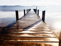 Wooden jetty. At a little lake in upper bavaria with mountains in background Stock Images