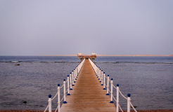 Wooden jetty off a tropical beach Stock Images