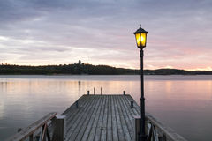 Wooden jetty with one lamp on it. Royalty Free Stock Photography