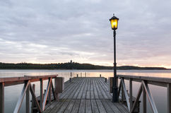 Wooden jetty with one lamp on it. Royalty Free Stock Image