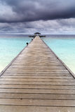 Wooden jetty over the beautiful Maldivian ocean Royalty Free Stock Image