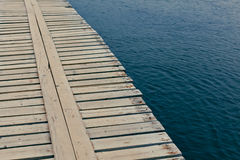 Wooden jetty over rippling water. Background of a deserted rustic wooden jetty made from planks of timber extending out over rippling water Stock Photo
