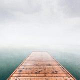 Wooden jetty, pier on deep cold sea, ocean. Raining sky. Scandinavian mood, copy-space stock image