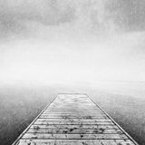 Wooden jetty, pier on deep cold sea, ocean. Raining sky. Scandinavian mood, copy-space. Black and white royalty free stock photography