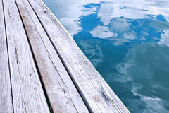 Wooden jetty pier and reflection of sky in blue water Royalty Free Stock Images