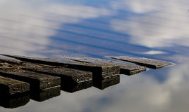 Wooden jetty with reflections. Wooden jetty in lake with reflections of clouds Stock Images