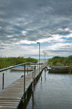 Wooden jetty in storm. Wood jetty in storm with boat at river stock images