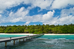 Wooden jetty to a tropical island. Wooden jetty to a beach of a resort on a tropical island with green lush vegetation in the Maldives Stock Photography