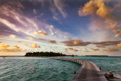 Wooden jetty towards a small island in Maldives at sunset stock image