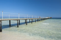 Wooden jetty on tropical beach. Wooden jetty structure going out to sea on tropical beach resort Stock Image
