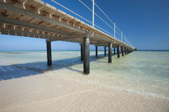 Wooden jetty on tropical beach. Wooden jetty structure going out to sea on tropical beach resort Stock Photo