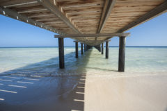 Wooden jetty on tropical beach. Wooden jetty structure going out to sea on tropical beach resort Stock Images
