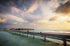 Wooden jetty and water villas. Maldives island resort at sunset royalty free stock images