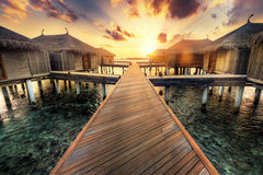 Wooden jetty and water villas. Maldives island resort at sunset. Wooden jetty towards water villas. Maldives island resort on Indian Ocean at sunset royalty free stock photography
