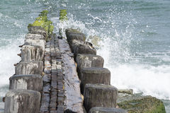 Wooden jetty with waves crashing over. Sunny day at a wooden jetting in the Atlantic ocean with waves crashing over it Royalty Free Stock Photo