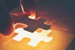 The wooden jigsaw puzzle is missing pieces that are ready to light.It is a business concept in component success.This image Soft royalty free stock photography