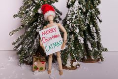 Wooden jointed mannequin doll holding sign Merry CATMAS wearing Santa Claus hat winter scene royalty free stock images